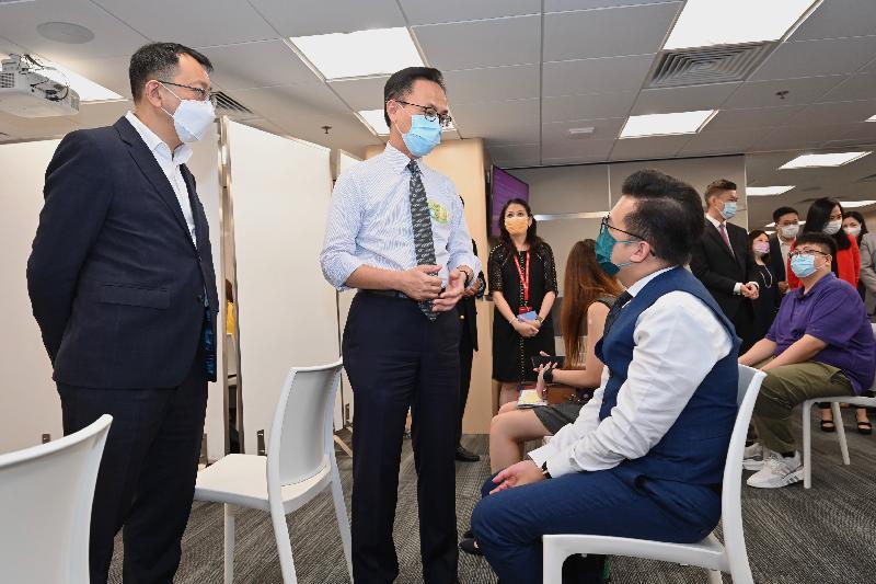 公務員事務局局長聶德權今日(八月三日)視察政府外展疫苗接種服務隊於友邦香港及澳門進行疫苗接種的情況。圖示聶德權(左二)和友邦香港及澳門營業總經理詹振聲(左一)與一名準備接種疫苗的人士交談。