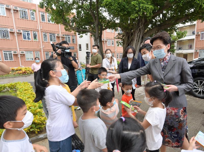 行政長官林鄭月娥今日(十月十日)到訪由九龍樂善堂營運的過渡性房屋項目。圖示林鄭月娥(右一)向小朋友派發糖果。